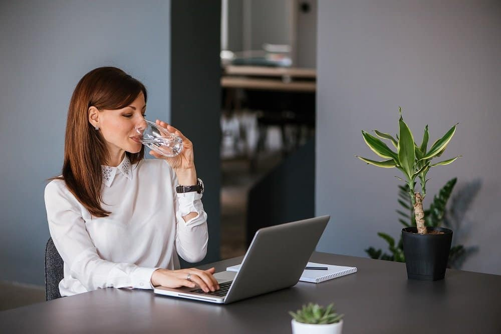 woman at desk drinking water